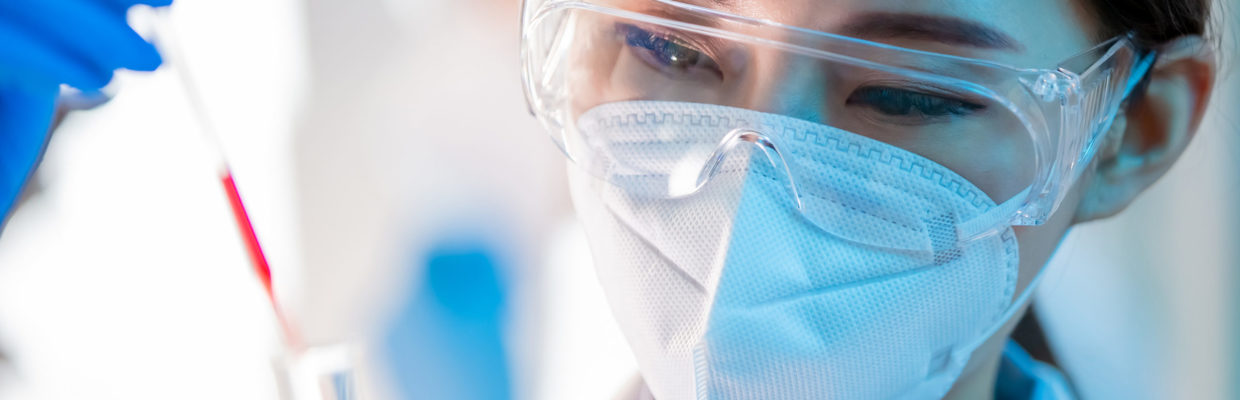 Researcher wearing PPE in a lab with a test tube.